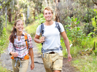 Outdoor activity couple hiking - happy hikers walking in forest.